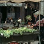 targ, starsza pani wybiera produkty, w tle dwaj mężczyźni siedzą przy stoliku