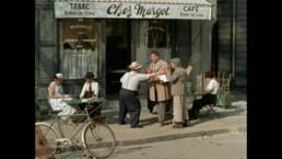 grupka mężczyzn rozmawia przed sklepem
