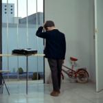 chłopiec stoi tyłem, teczka przed nim, z tyłu rower