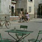 stolik w oddali siedząca para i rower