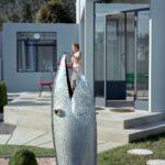 rzeźba pionowo sterczjącej ryby na tle stojącej kobiety