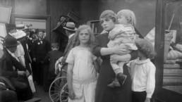 kobieta z dwójką dzieci, jedno z nich trzyma na rękach