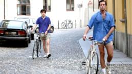dwóch mężczyzn prowadzi rower włoską uliczką