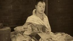 zaspany mężczyzna siedzi na łóżku