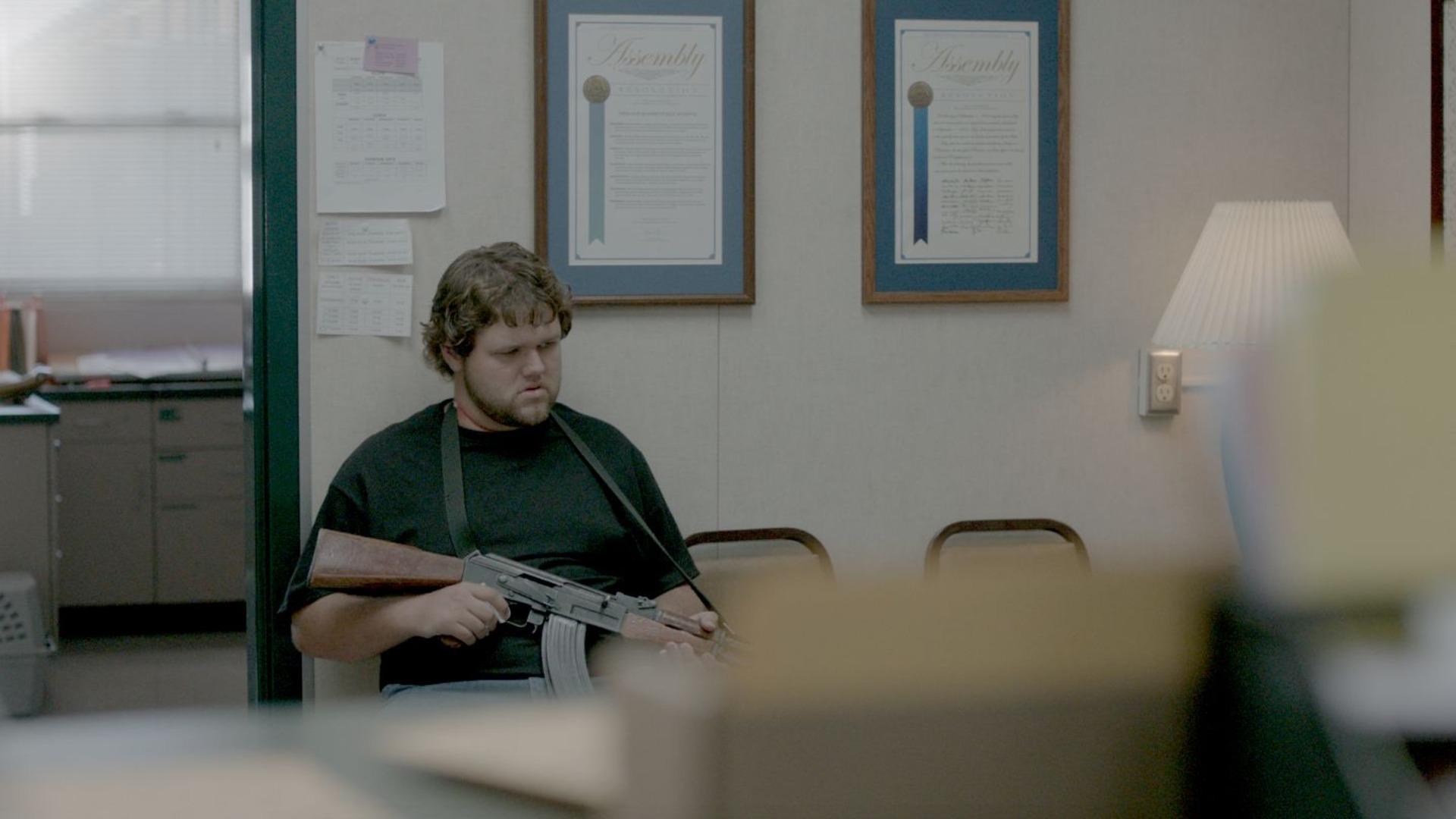 chłopak z bronią siedzi w szkolnym sekretariacie