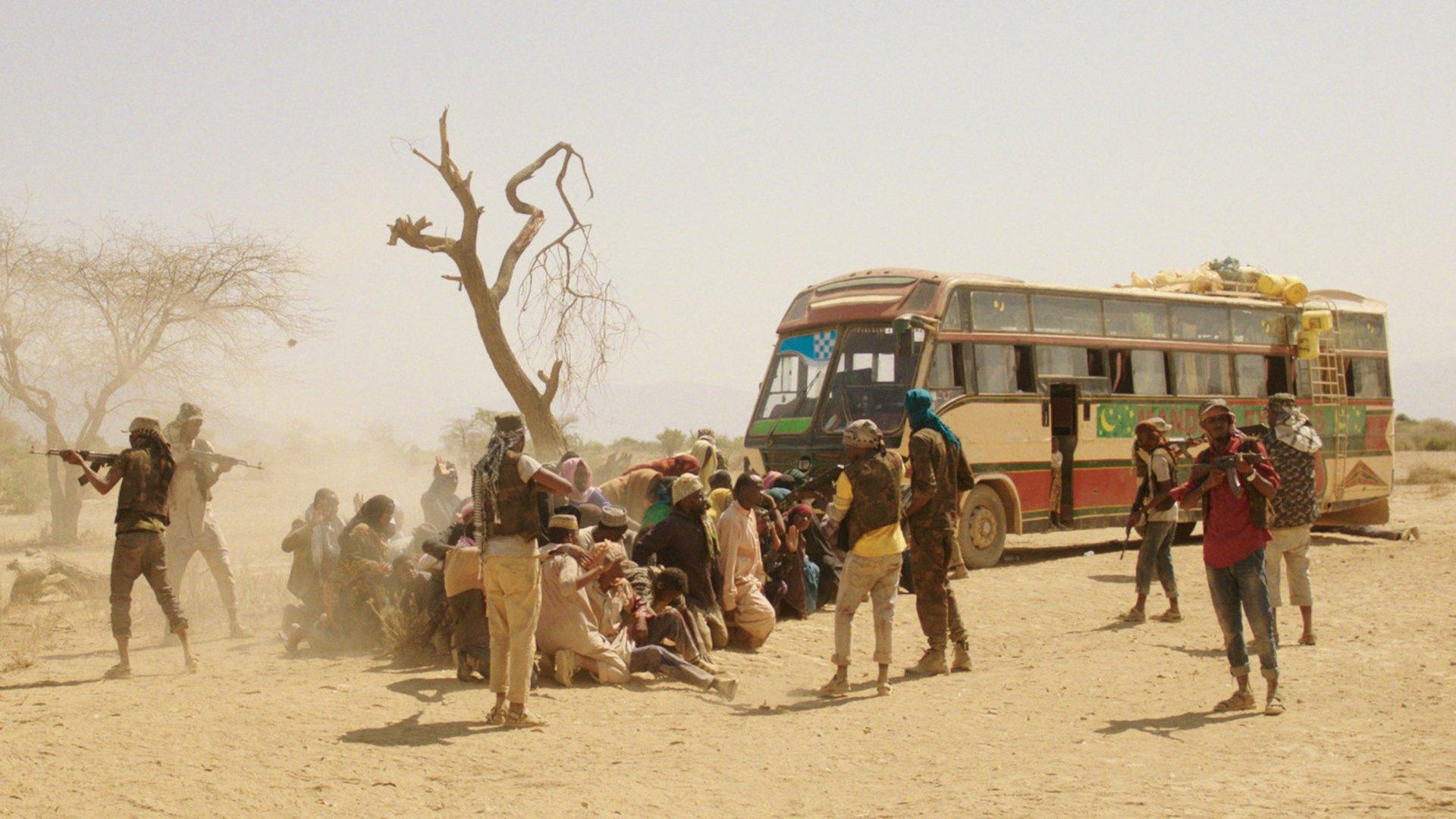 grupa terrorystów celuje bronią w zakładników na tle autobusu