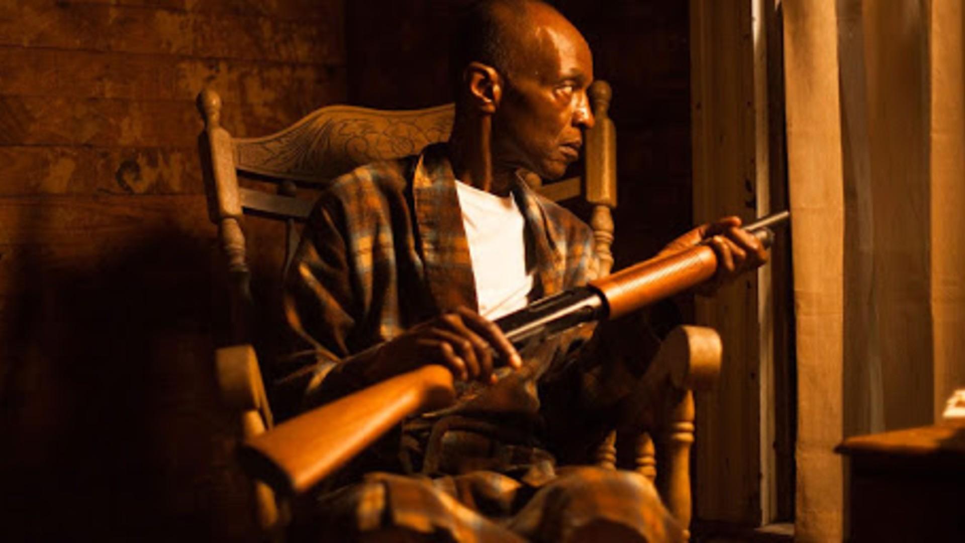 afroamerykanin siedzi ze strzelbą i wypatruje czegoś